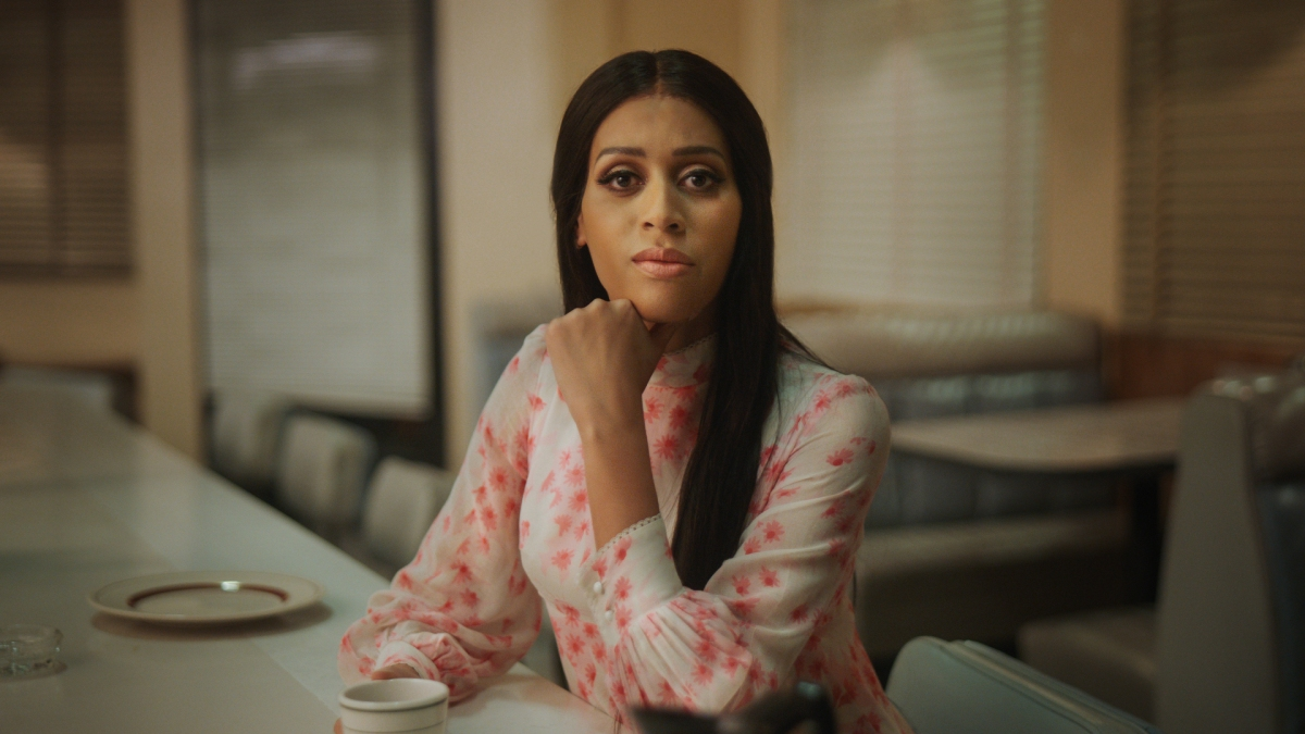 Isis King as Alexis. Sitting a a counter at a cafeteria in a flowered shirt.