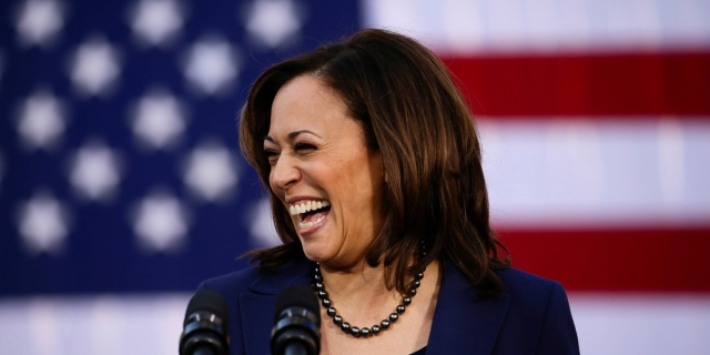 Kamala Harris smiles off to the side in front of the United States flag. Her resemblance to Bette Porter running for Mayor of Los Angeles is uncanny.