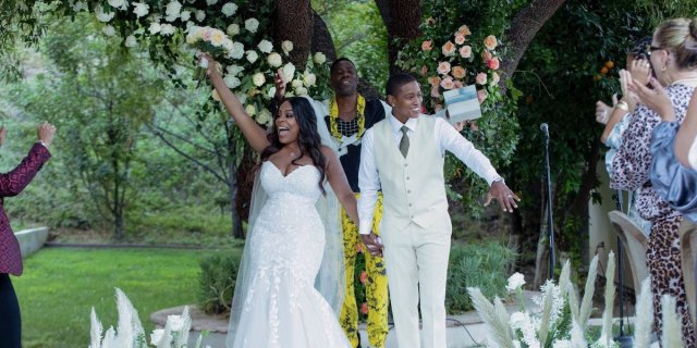 Niecy Nash getting gay married to new wife Jessica Betts. Niecy is in a white mermaid gone and Jessica wears a white suit and matching sneakers.