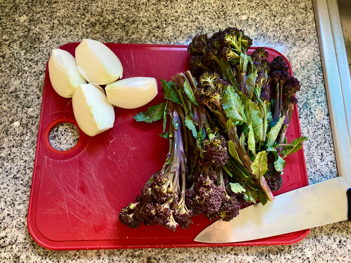 On a red cutting board, a white onion is quartered and two bunches of broccolini with their edges trimmed, are lying next to a knife