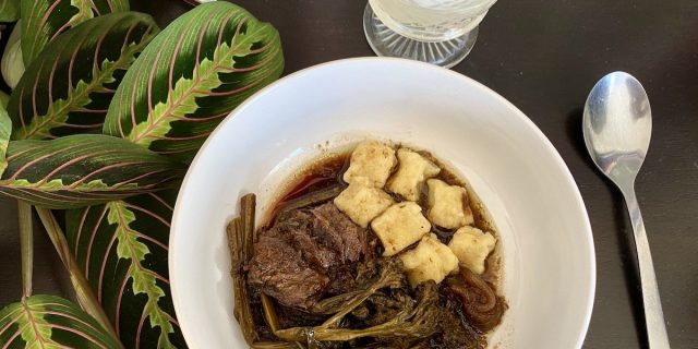 A bowl of braised beef, broccolini, and ricotta gnocchi sits on a black surface, and the leaves of a prayer plant snuggle up against it. A spoon sits next to the bowl and a cut crystal glass peeks into the edge of the frame. It's time to eat.