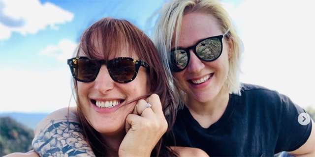 "Jen Richards and Rebekah Cheyne are posing for their engagement photo. Both are wearing sunglasses and Jen's hand is in a fist near her cheek, showing off her engagement ring. They are both smiling like ""Love wins"" after all!"