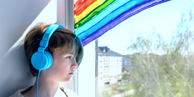 A sad teenage lesbian full of loneliness and missing her friendships, listening to a playlist on her iPhone while looking out a window with a handprinted rainbow on it.