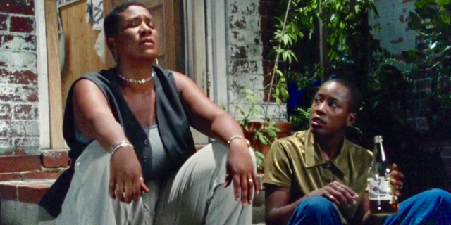 A still from Cheryle Dunye's The Watermelon Woman. Two black queer women sit on a stoop at night, talking with each other.