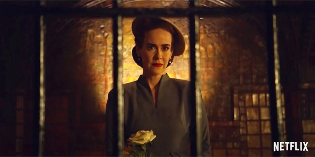 Sarah Paulson as Nurse Ratched stares horrifically behind bars in captivity, with bricks behind her glowing yellow.