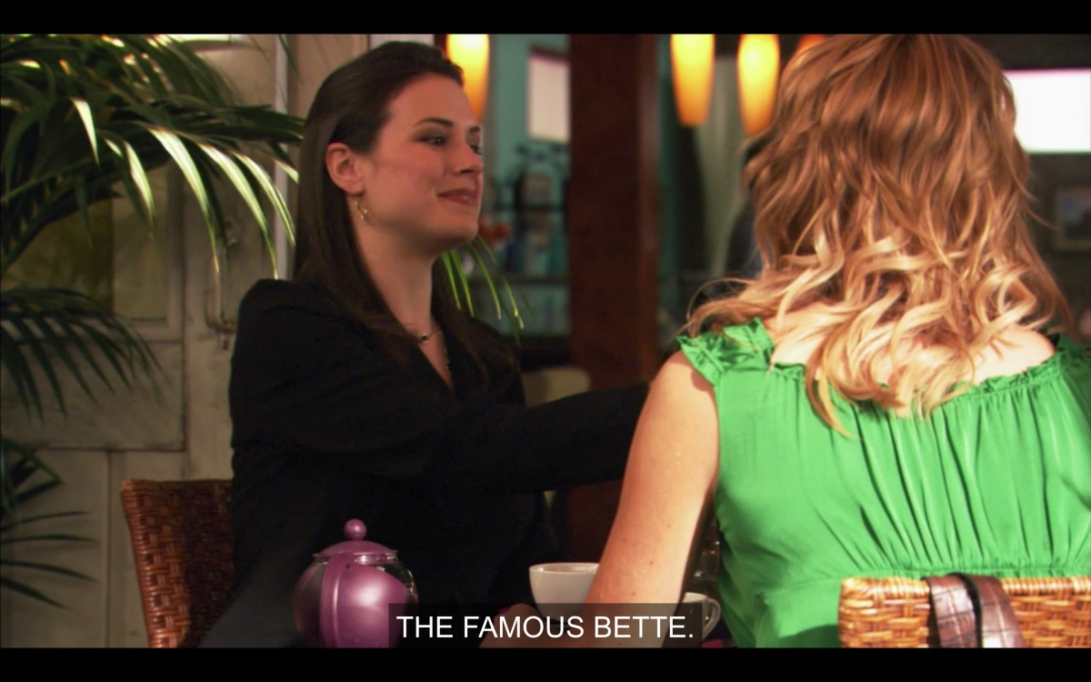 """Denise, a woman with slicked-back hair and a black blazer, is sitting at a table at The Planet with Tina, saying """"the famous Bette"""""""