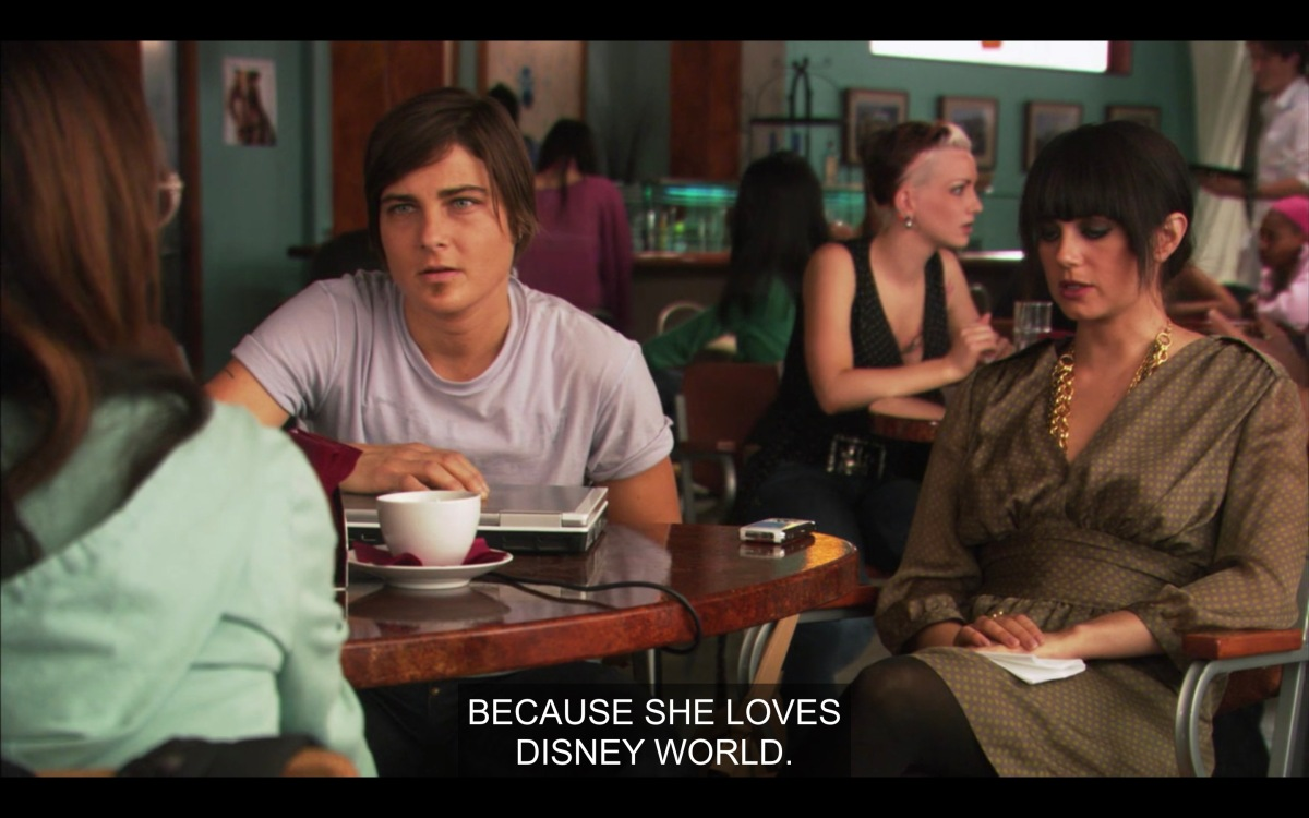 """Max and Jenny are sitting at a table at The Planet with Adele, whose back is to the camera. """"Because she loves Disney World."""""""