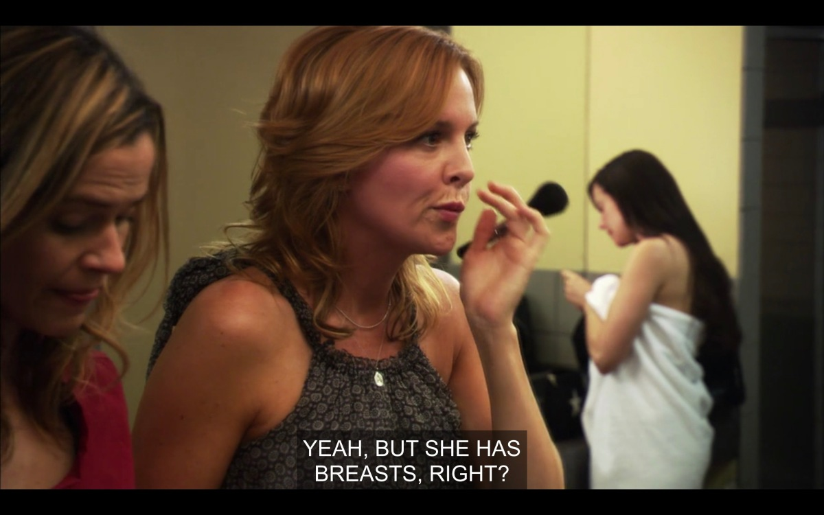 """Tina and Alice doing their makeup. Tina says, """"yeah, but she has breasts, right?"""""""