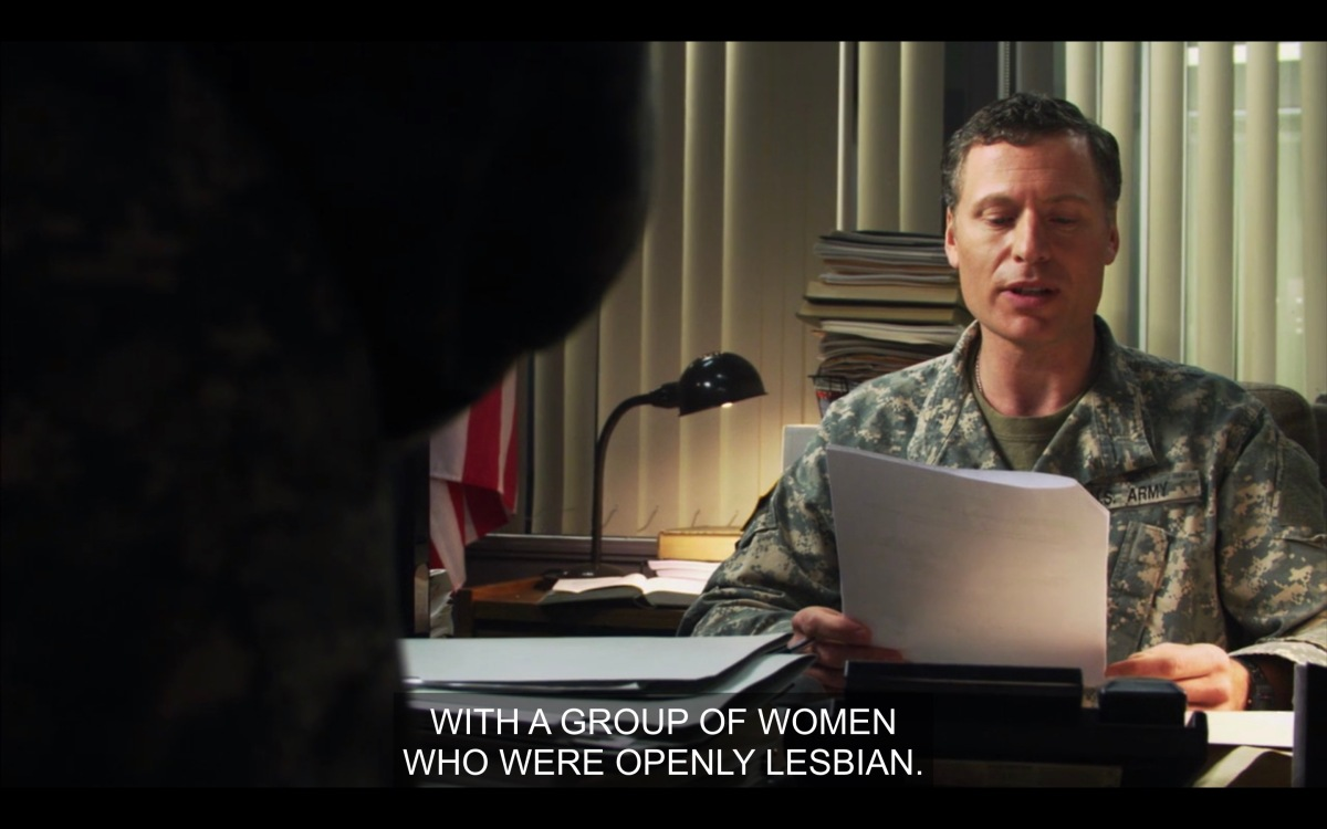 """Beech in his office at the military base reading from a package of papers, """"with a group of women who were openly lesbian"""""""