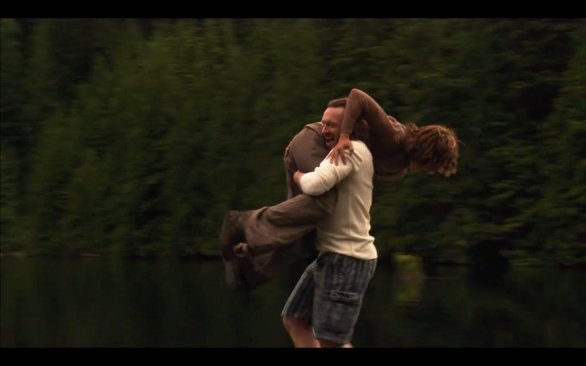 A terrible man carries Bette on his shoulder, about to throw her into the lake