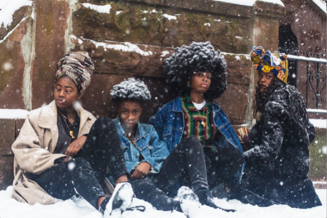 Four African Women sit in the wet snow against a brick wall. One woman has a brown headless and light brown wool coat. Two women have afros, covered in snow so they look more like crowns, and denim jackets. The last woman has a black hoodie wool coat and multi-colored head wrap.