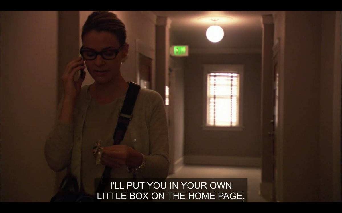"""Alice in the hallway of her apartment building, saying """"I'll put you in your own little box on the home page"""" to Max on the phone"""