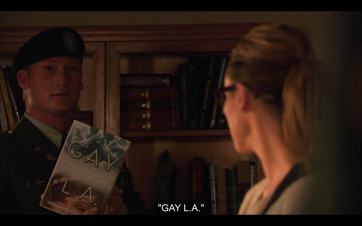 """A solider takes the book """"Gay LA"""" off of Alice's bookshelf and reads the title out loud"""