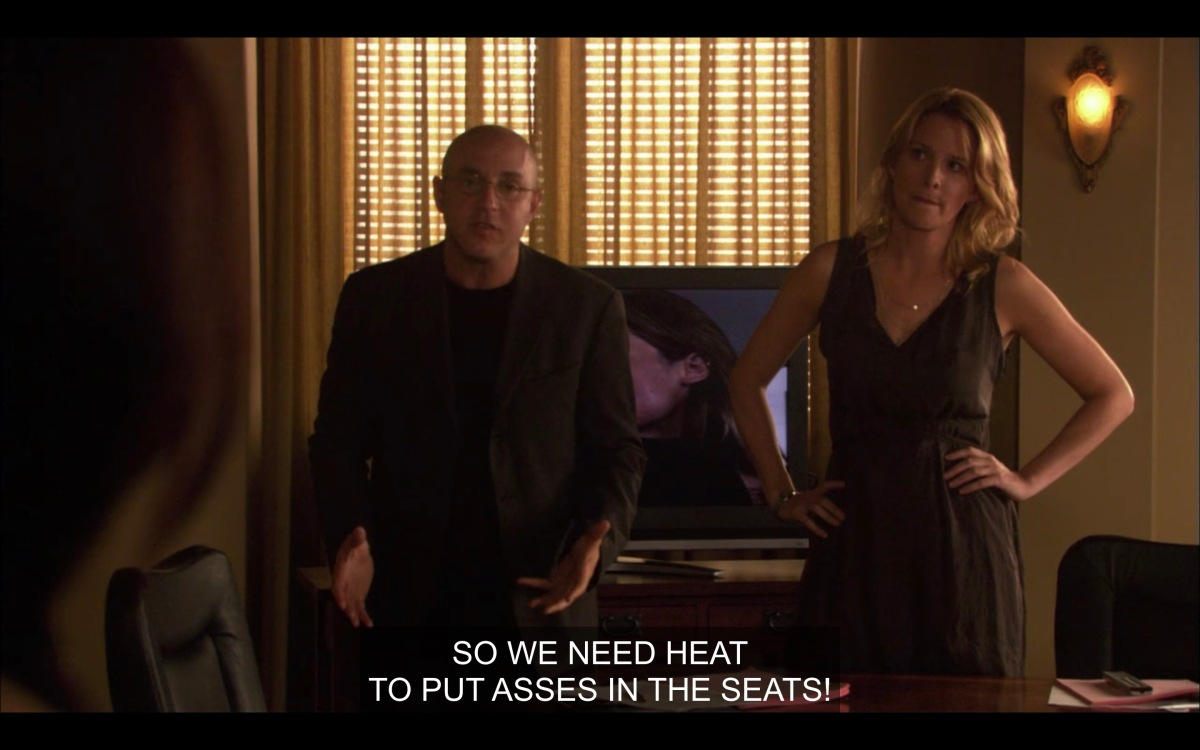 """Conference room. Tina and Aaron standing in front of a television where audition tapes are playing, saying """"So we need heat to put asses in the seats."""""""