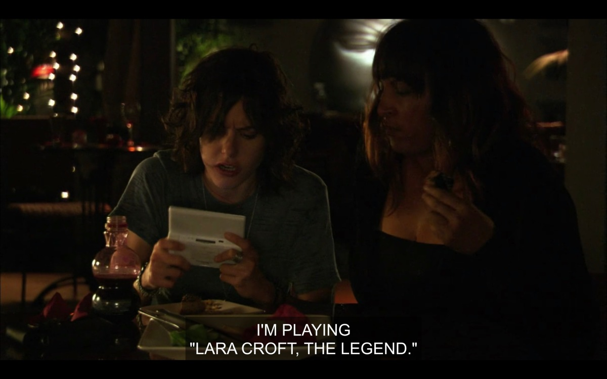 """Shane plays a video game while eating, Kit sitting next to her. Shane says """"I'm playing Lara Croft, the Legend"""""""