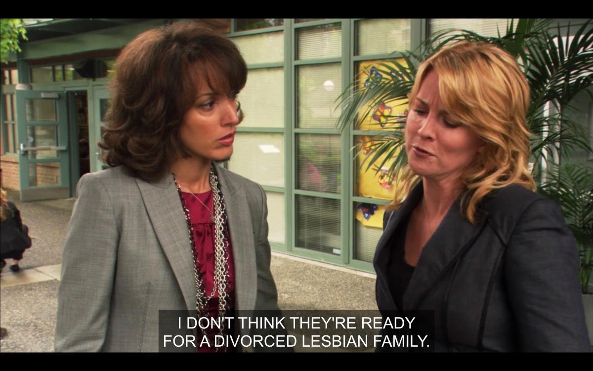 Bette, in a magenta shirt and a grey blazer, is looking at Tina, they are standing outside a preschool and Tina is saying that they're not ready for a divorced lesbian family.