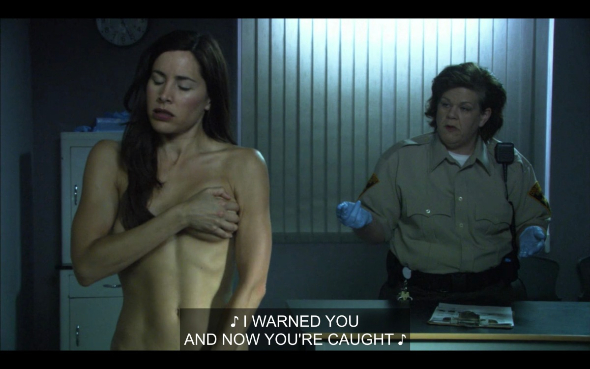 Helena Peabody is holding her arm over her breasts while naked in a strip-search room before going to jail. The cop behind her is telling her something she doesn't like.