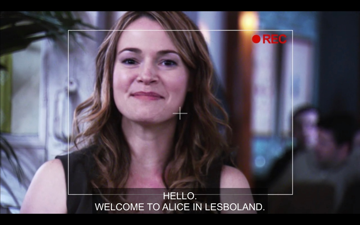 """Looking through the camera at Alice, who is happy and saying """"Hello, Welcome to Alice in Lesboland."""" They're at The Planet."""