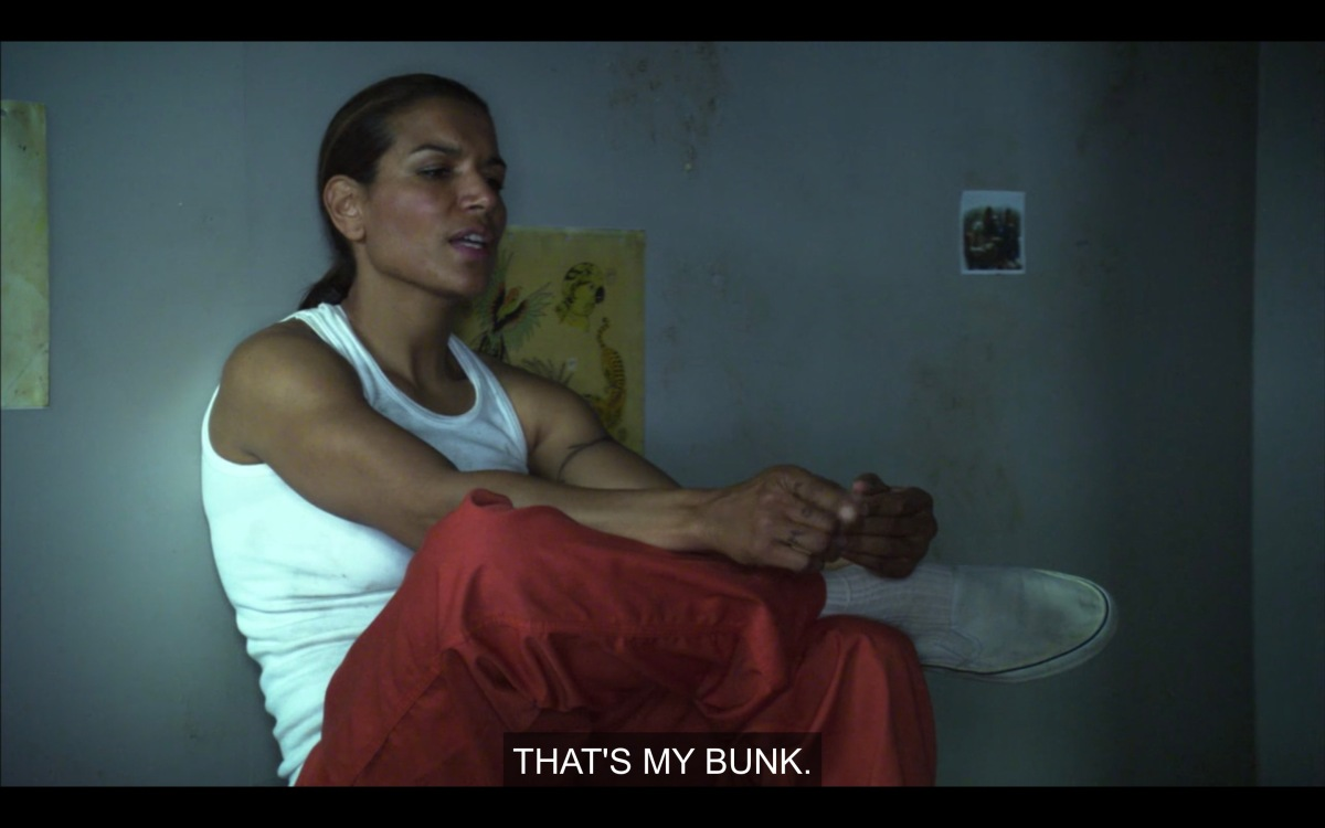"""Jail cell. Dusty is wearing a tank top and orange prison pants. She is sitting on a table and telling Helena """"That's my bunk."""""""