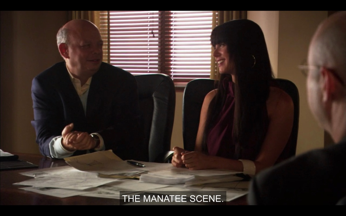 """William and Jenny at a board meeting, with lots of papers in front of them. Looking admiringly at Jenny, Williams says """"The Manatee scene."""" Jenny is wearing a purple dress and has severe bangs."""