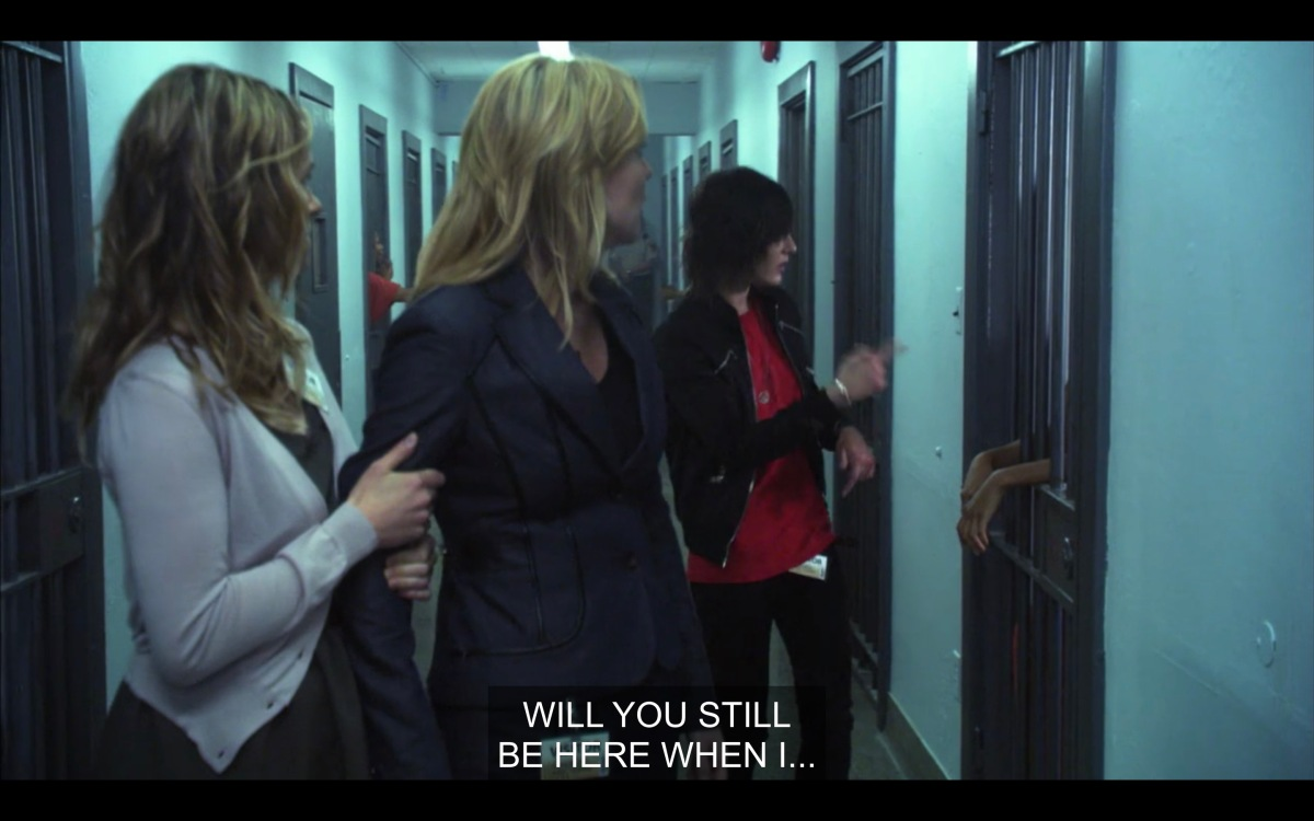 Shane is hitting on an inmate while walking down a hallway in jail. Alice and Tina are looking back at her