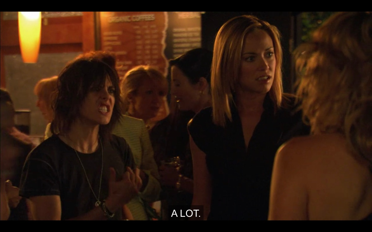 At a party. Shane's teeth are gritted, she's wearing a t-shirt, she's holding her hand out in some gesture while Paige, aghast, looks at her friends for support.