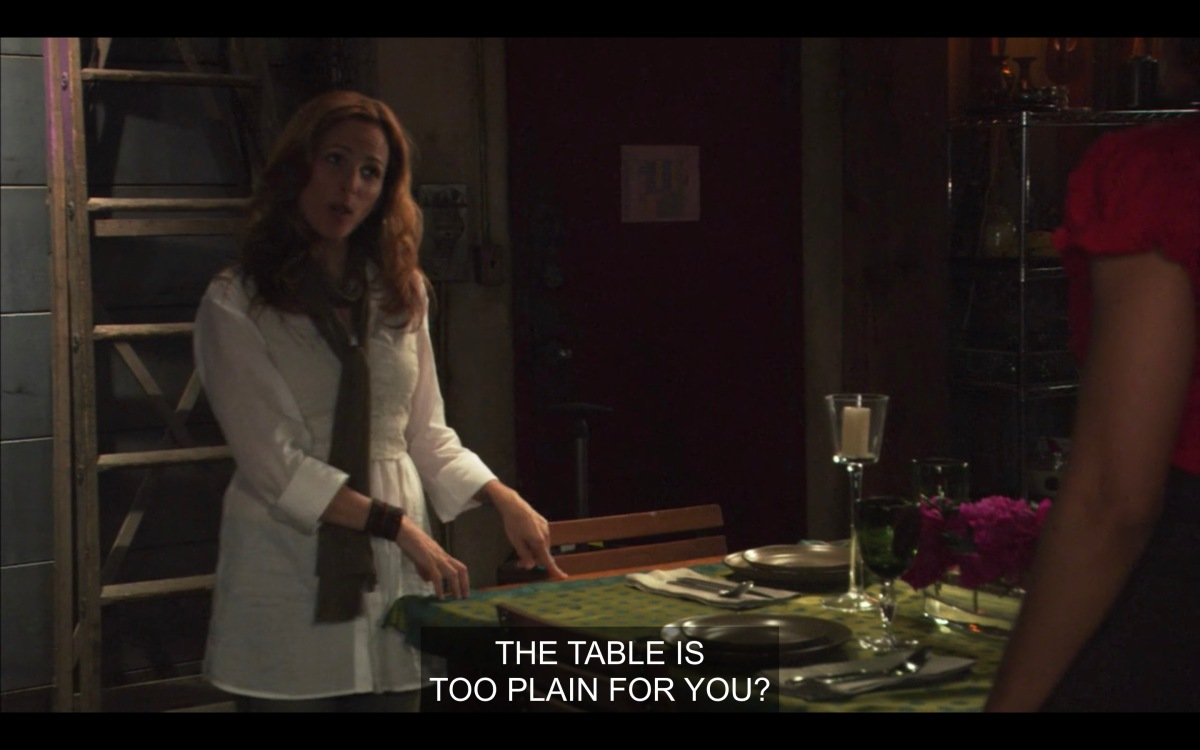 """Jodi gestures towards the table in her loft, which is set with a green tablecloth and place settings. Jodi is wearing a white shirt and scarf and gesturing towards the table saying """"the table is too plain for you?"""""""
