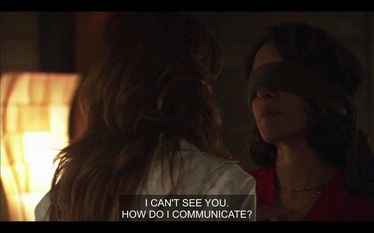 """Jodi's back is to the camera, we can see Bette with a blindfold on. She is saying """"I can't see you, how do I communicate"""""""