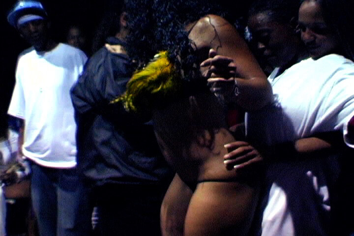 a Black woman in a g string and a sexy feathered top dances for a client in a white t-shirt, who is putting a hand on the dancing woman's waist