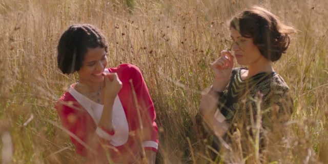 Gemma Arterton as Alice and Gugu Mbatha-Raw as Vera, sitting together in a field laughing in the film Summerland.