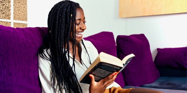 A cheerful young black woman with long braided hair is reading a thick book on a purple couch.