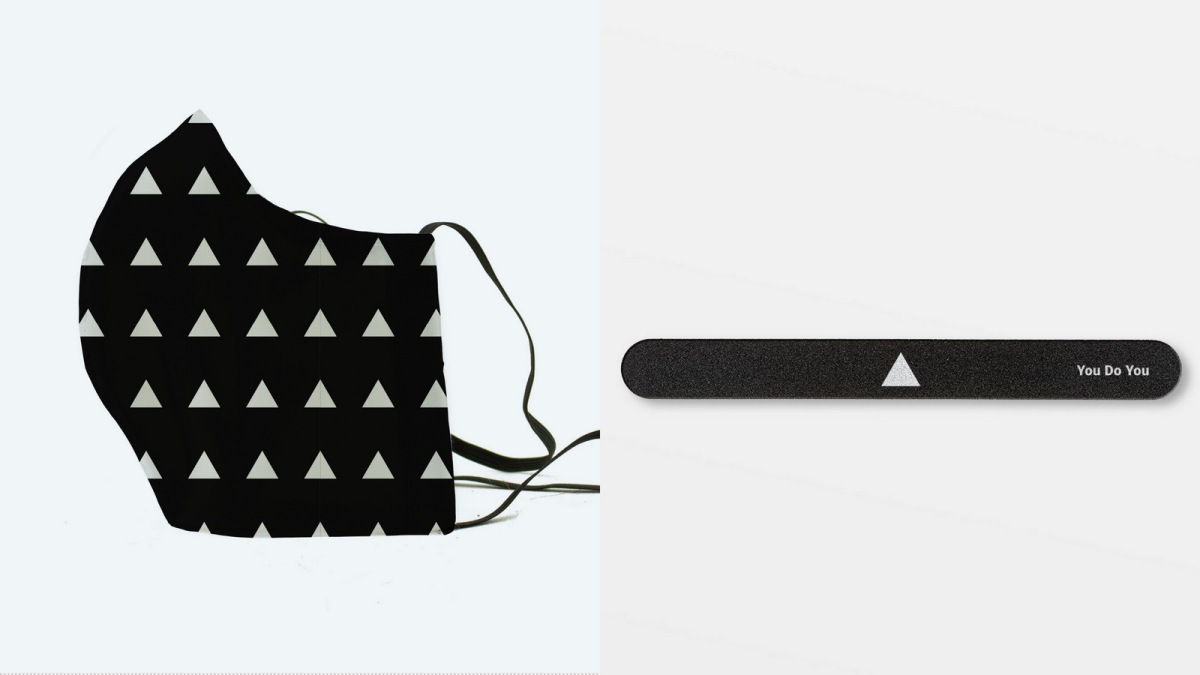 The white Autostraddle triangle finds a home on a black face mask and a nail file.