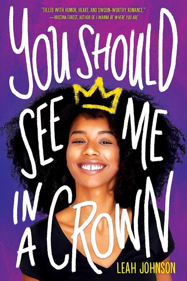 "The ""You Should See Me in a Crown"" cover is bright purple and fuchsia. There's a teenage Black girl with a big afro smiling in the middle. She has a graffiti yellow crown drawn delicately upon her head."