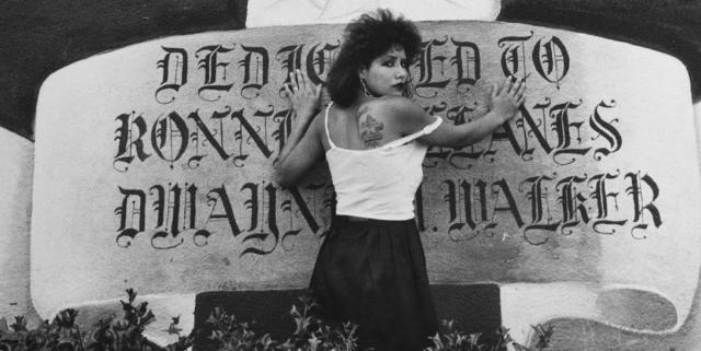 "A tough and pretty chola woman, with the top of her hair teased and dark lipstick, places both of her hands on a huge painted mural banner and looks over her shoulder with anguish and ""don't fuck with me"" energy. She is looking over her shoulder and the top of her white tank top is pulled to the side showing off a tattoo. The banner, in a stylized script reads: ""Dedicated to Ronnie ..anes Dwayne Walker."""