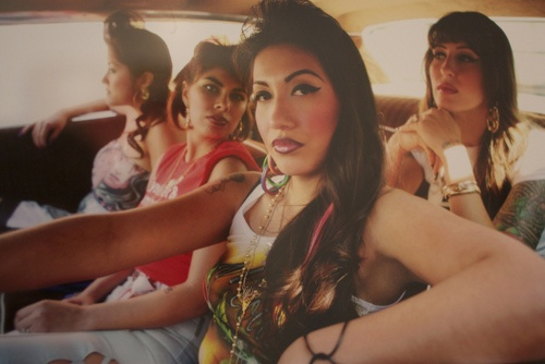 four chola women ride inside of a car together. the one in the driver's seat has a hand on the wheel, an elbow perched on the window sill and a made up face with winged eyeliner and dark lipliner