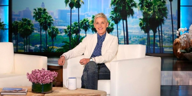 Ellen Degeneres on the set of her talks show, seated and smiling at the camera.