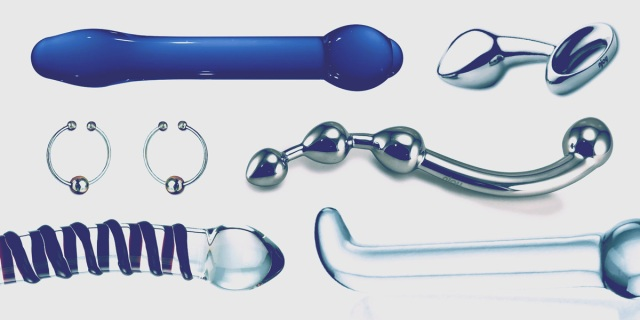 A collage of sex toys, including an array of glass dildos, nipple rings, a stainless steel wand toy and a stainless steel butt plug, all edited with a cool blue cast