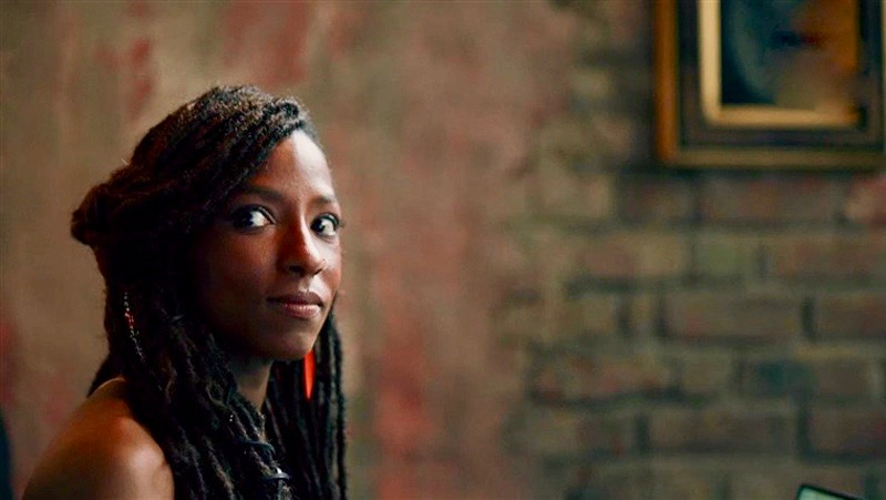 """Nova Bordelon from """"Queen Sugar"""" sits thoughtfully alone in a chair in front of a brick wall that is full of rich, warm tones."""