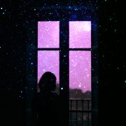 woman staring out a window to the outdoors