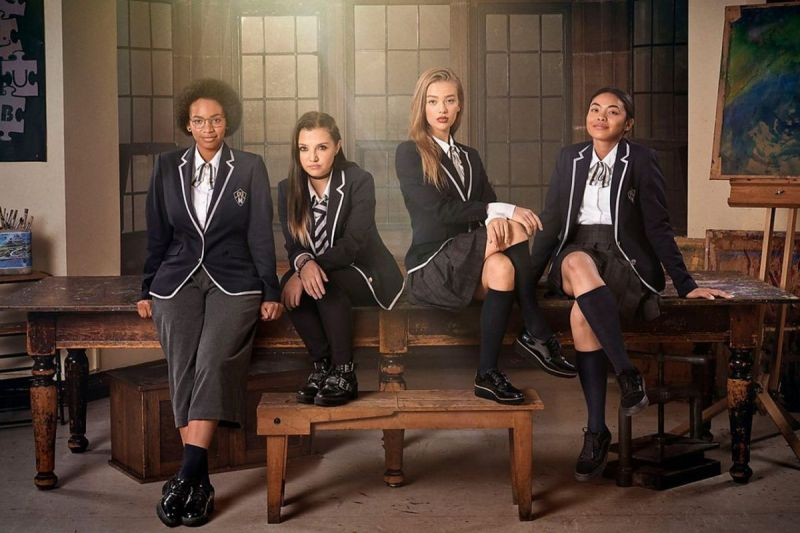 Four girls in school uniforms sit on a table in a smoky room: Margot (Black, wearing glasses and short pants), Bree (white, with a half-braided hair situation), Olivia (your standard white blonde blue-eyed pretty girl) and Kitty (athlete, ponytail, skirt)