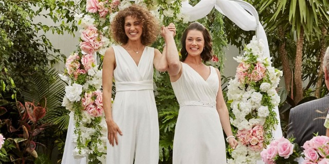 Two lesbians in wedding gowns holding their hands triumphantly in the air in the new Hallmark movie Wedding Every Weekend.