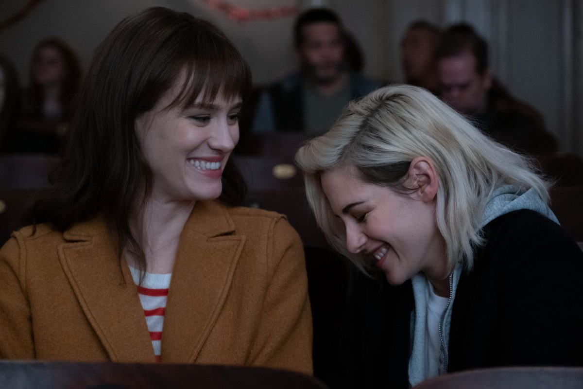 "A screenshot of ""Happiest Season"" in which Kristen Stewart smiles at Mackenzie Davis. This is a lesbian movie available for streaming on Hulu."