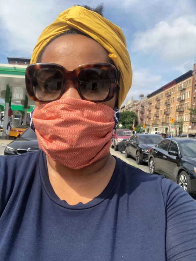 Jehan living New York city on moving day, she has a orange face bask and dark sunglasses and a yellow head wrap.