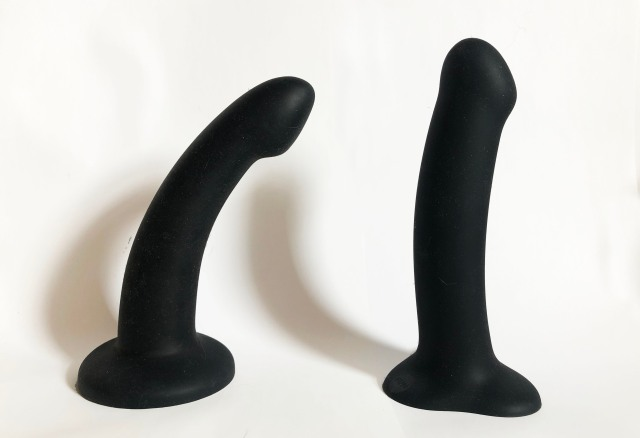 On the left, a curved, slightly tapering black dildo with a wide, solid circular base; on the right, a straighter, thicker black dildo with a straight shaft