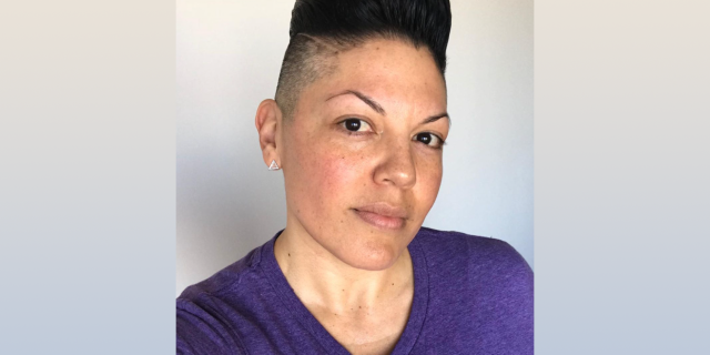 A photo of Sara Ramirez in a purple t-shirt on the day that they came out as non-binary.