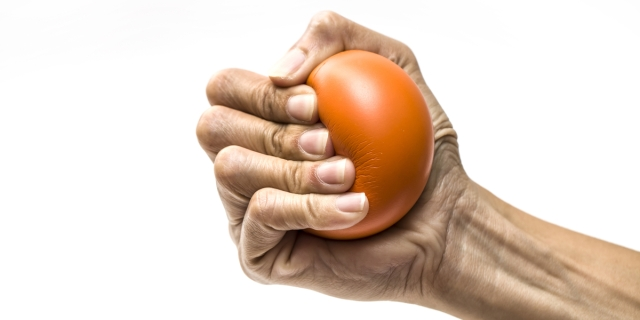 a hand grips an orange stress ball