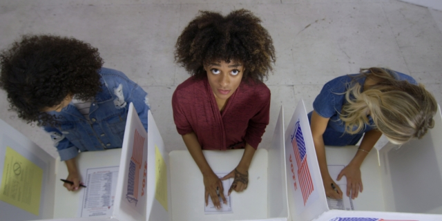 Three women at voting booths. The woman in the center is looking up at the camera, concerned.