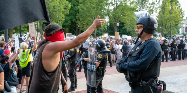 A standoff in Kenosha between protestors on the left and police in riot gear on the right; in the foreground, a white person wearing a red bandana as a mask gestures angrily at a cop, who looks on impassively