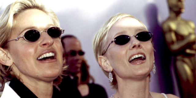 Anne Heche and Ellen DeGeneres standing together on a red carpet in 1997.