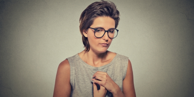 A thin white person with short hair is in the center of the frame, pictured from the waist up wearing a gray tank top and glasses; their shoulders are slightly hunched and they look off and to the side as if worried or tired.
